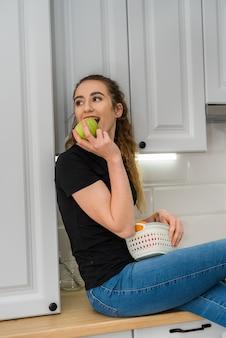 Schöne junge frau, die frische früchte am frühstück einen frühen morgen in der küche, diät isst. weiblicher lebensstil