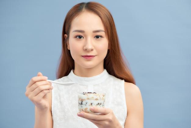Schöne junge frau, die frischen joghurt, rosinen und haferflocken zum frühstück isst.