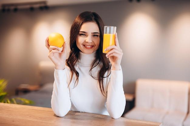 Schöne junge frau, die frischen orangensaft in der küche trinkt. gesunde ernährung.
