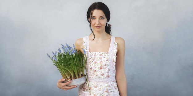 Schöne junge frau, die frühlingsblumen im blumentopf hält, der die front betrachtet