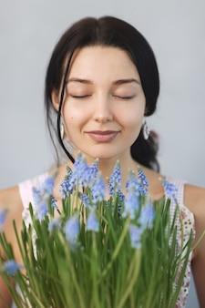 Schöne junge frau, die frühlingsblumen mit geschlossenen augen riecht