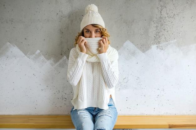 Schöne junge frau, die gegen wand sitzt und weißen pullover, strickmütze und schal trägt