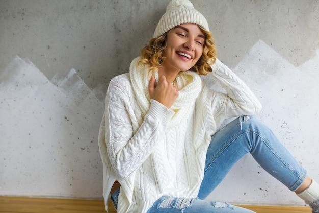 Schöne junge frau, die gegen wand sitzt und weißen pullover und jeans, strickmütze und schal trägt