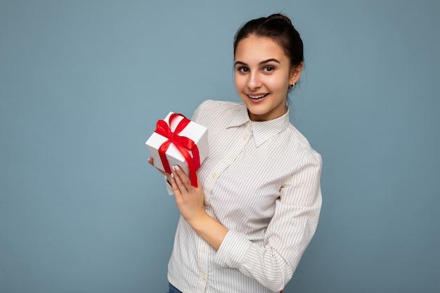 Schöne junge frau, die geschenkbox hält