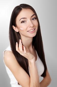 Schöne junge frau, die gesichtscreme an ihrem wangenknochen in einer schönheitshautpflege oder -kosmetik auf grau mit kopienraum aufträgt