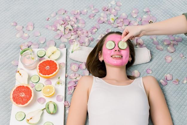 Schöne junge frau, die gesichtsmaske der gurke im schönheitssalon, hände der kosmetikerin empfängt