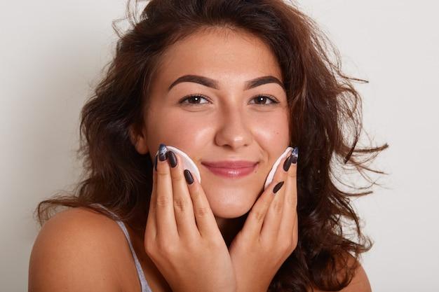 Schöne junge frau, die gesichtsreiniger anwendet, entzückende frau ohne make-up, dame, die lokal auf weiß aufwirft