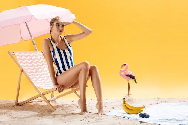 Schöne junge frau, die gestreiften badeanzug trägt, lokalisiert über gelbem hintergrund
