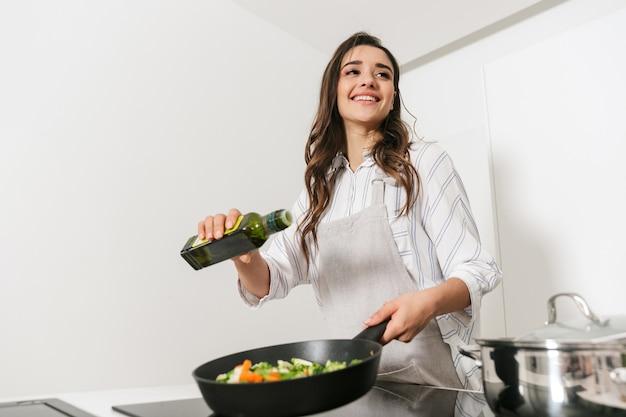 Schöne junge frau, die gesundes abendessen an der küche kocht, unter verwendung der bratpfanne