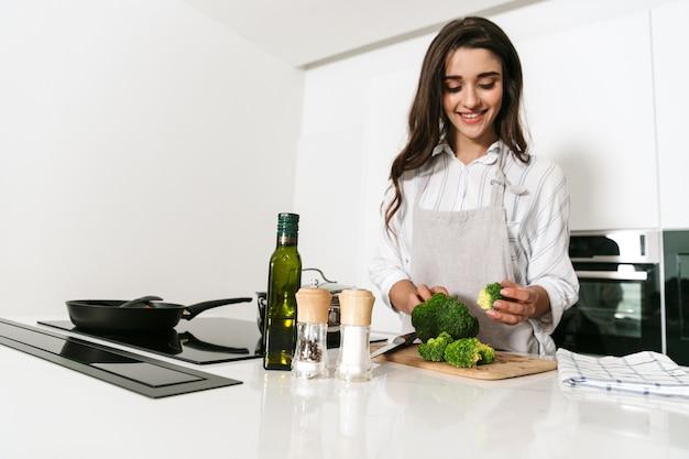 Schöne junge frau, die gesundes abendessen an der küche kocht