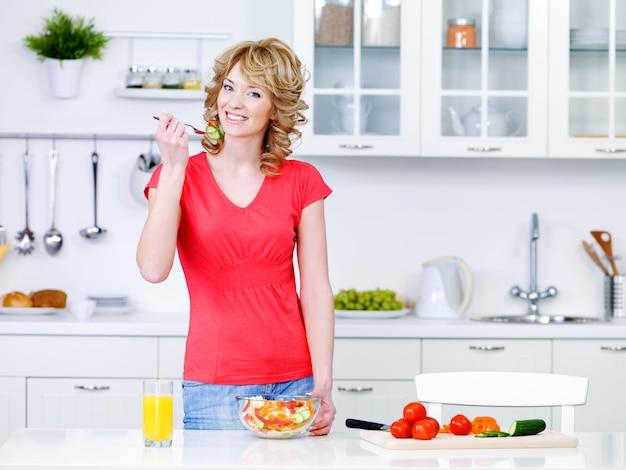 Schöne junge frau, die gesundes essen kocht und salat in der küche isst