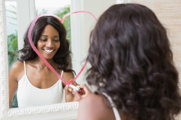 Schöne junge frau, die großes herz auf spiegel zeichnet
