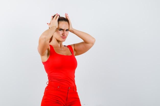 Schöne junge frau, die hände auf kopf in rotem trägershirt, hosen und schauen deprimiert, vorderansicht hält.