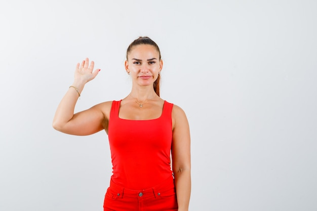 Schöne junge frau, die hand für begrüßung im roten trägershirt, in der hose und im selbstbewusstsein winkt. vorderansicht.