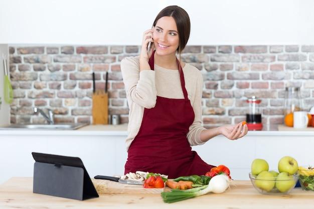 Schöne junge frau, die handy beim kochen in der küche verwendet.