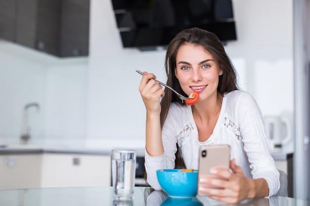 Schöne junge frau, die handy verwendet, während salat in der küche macht. gesundes essen. gemüsesalat. diät. gesunder lebensstil. zu hause kochen.