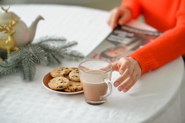 Schöne junge frau, die heiße schokolade zu hause am heiligabend, nahaufnahme trinkt
