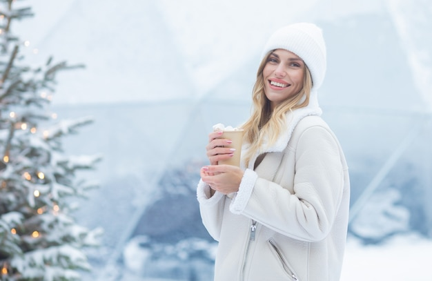 Schöne junge frau, die heißen kakao draußen trinkt. weihnachten.