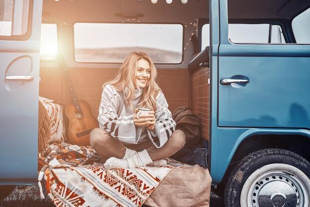 Schöne junge frau, die heißes getränk genießt und lächelt, während sie zeit im retro-minivan verbringt?