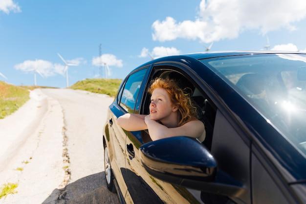 Schöne junge frau, die heraus autofenster schaut
