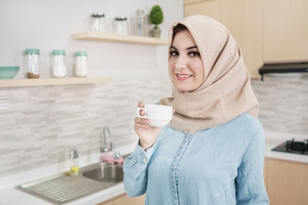 Schöne junge frau, die hijab trägt, der eine tasse kaffee trinkt