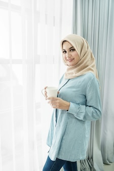 Schöne junge frau, die hijab trägt, während eine tasse tee trinkt