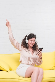 Schöne junge frau, die hörende musik des smartphone auf kopfhörer betrachtet