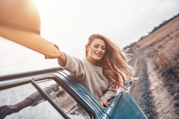 Schöne junge frau, die hut trägt und glücklich aussieht, während sie einen roadtrip im minivan genießt?