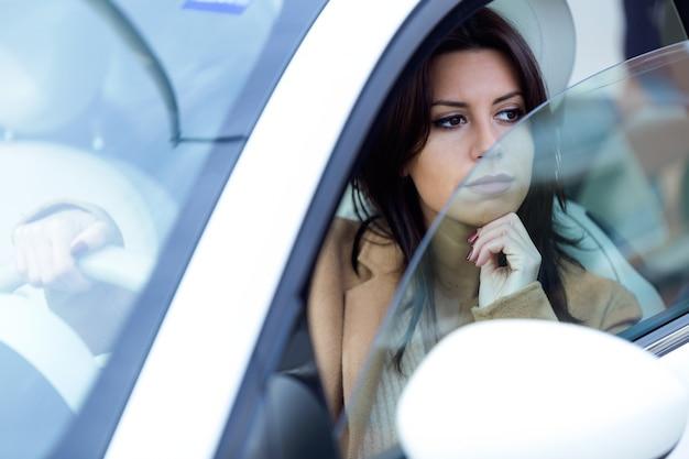 Schöne junge frau, die ihr auto antreibt.