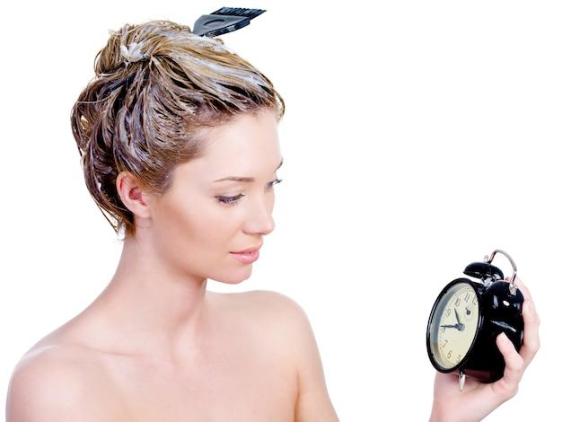 Schöne junge frau, die ihr haar färbt und auf uhr schaut - lokalisiert auf weiß