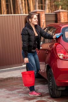 Schöne junge frau, die ihr kleines rotes auto wäscht