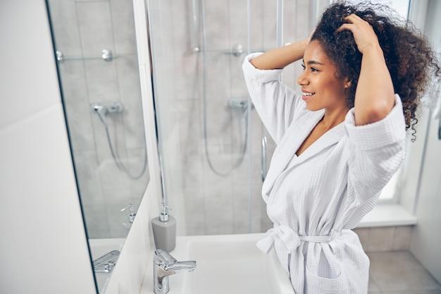 Schöne junge frau, die ihr lockiges dunkles haar vor dem spiegel untersucht