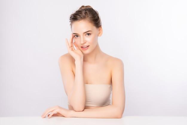 Schöne junge frau, die ihr sauberes gesicht mit frischer gesunder haut berührt, lokalisiert auf weiß