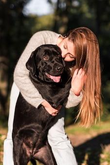 Schöne junge frau, die ihr schwarzes labrador im park küsst