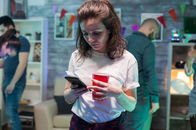 Schöne junge frau, die ihr smartphone auf der party ihrer freundin benutzt und einen bierbecher hält.