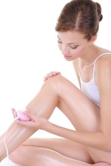 Schöne junge frau, die ihre beine mit rasierer rasiert - körperpflege