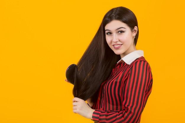 Schöne junge frau, die ihre haare kämmt