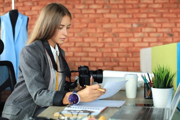 Schöne junge frau, die ihre notizen betrachtet und digitalkamera beim sitzen in ihrer werkstatt hält.