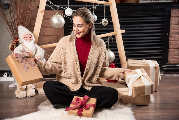 Schöne junge frau, die ihre weihnachtsgeschenke zu hause hält