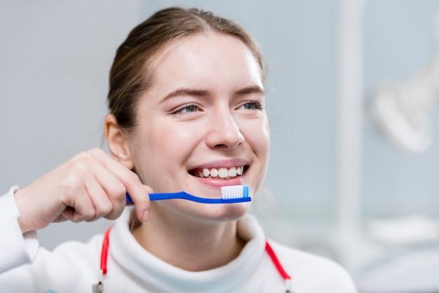 Schöne junge frau, die ihre zähne putzt