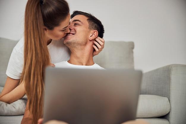 Schöne junge frau, die ihrem mann einen kuss gibt