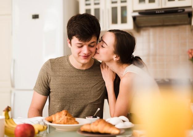 Schöne junge frau, die ihren freund küsst