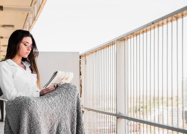 Schöne junge frau, die im balkon liest die zeitung sitzt