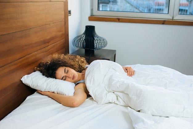 Schöne junge frau, die im bett schläft.