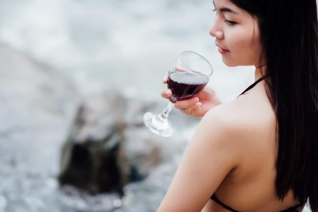 Schöne junge frau, die im im freien trinkendes cocktail sitzt und den fluss aufpasst