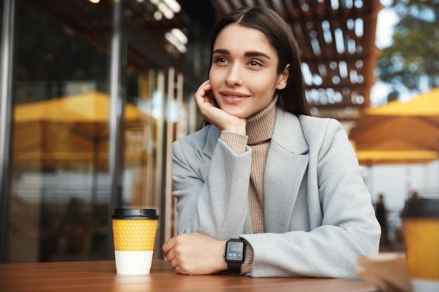 Schöne junge frau, die im mantel und in der smartwatch sitzt und in einem café wartet.