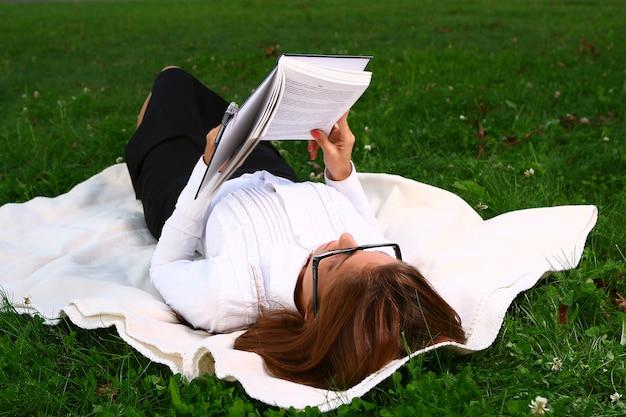 Schöne junge frau, die im park studing ist