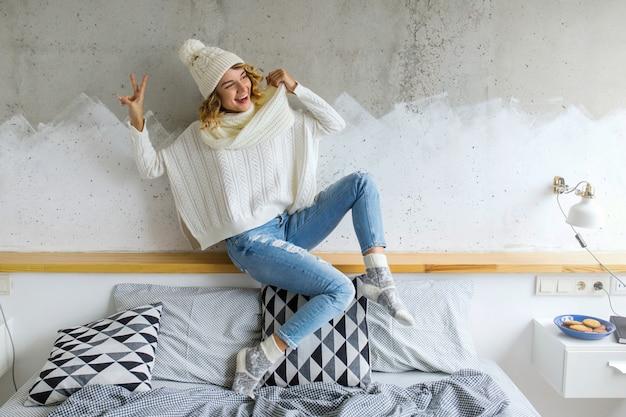 Schöne junge frau, die im schlafzimmer gegen wand trägt weißen pullover sitzt