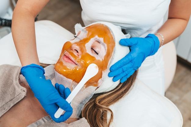 Schöne junge frau, die im spa-schönheitssalon eine gesichtsmaske mit verjüngenden effekten erhält.