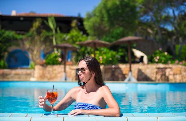 Schöne junge frau, die im swimmingpool mit geschmackvollem cocktail sich entspannt